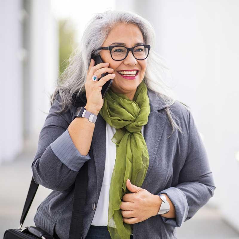 Satisfied hearing aid user talking on phone