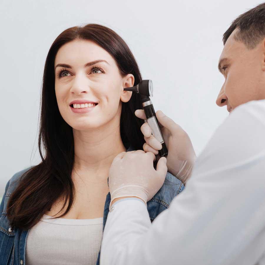 Hearing Expert examining a woman's ear